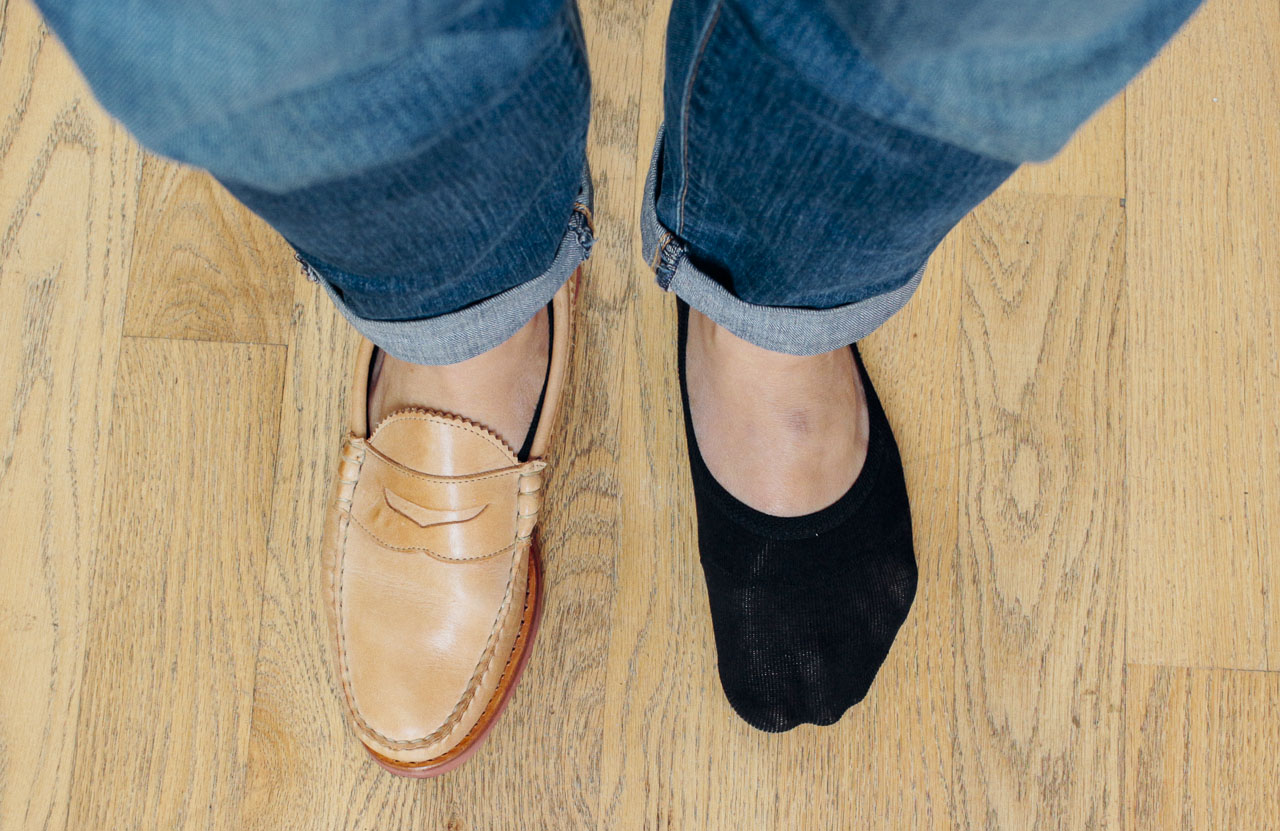 man with one shoe on, one shoe off, with no show socks