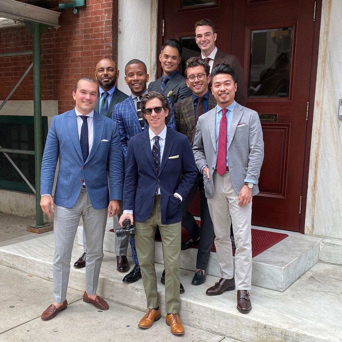 group of men wearing suit jackets and ties standing in front of brown door