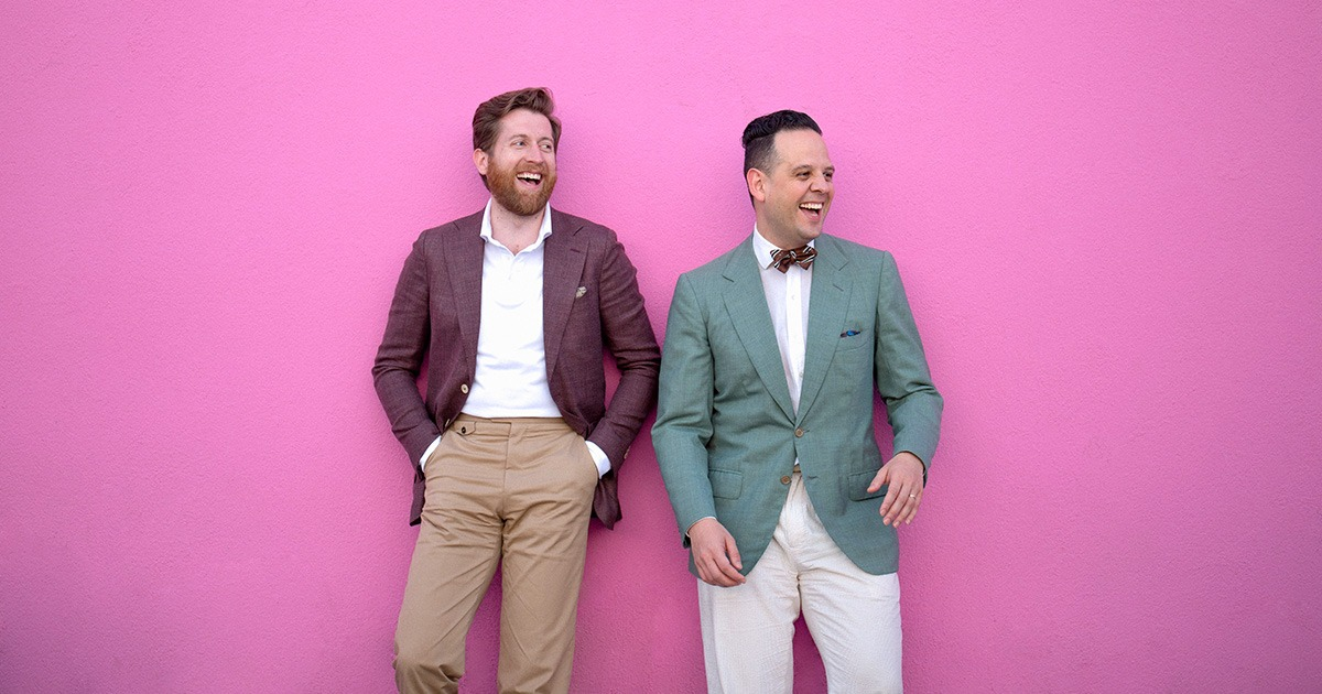 two man in suit jackets standing against a pink wall