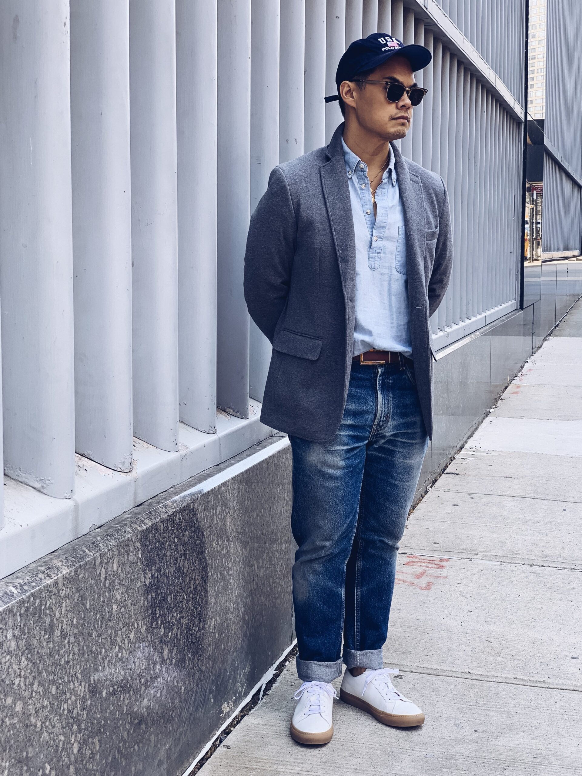 man wearing white sneakers with blue jeans light blue button down shirt and grey sportcoat with blue baseball cap