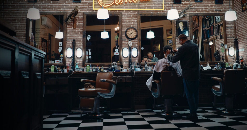 dimly lit barbershop with one barber and customer
