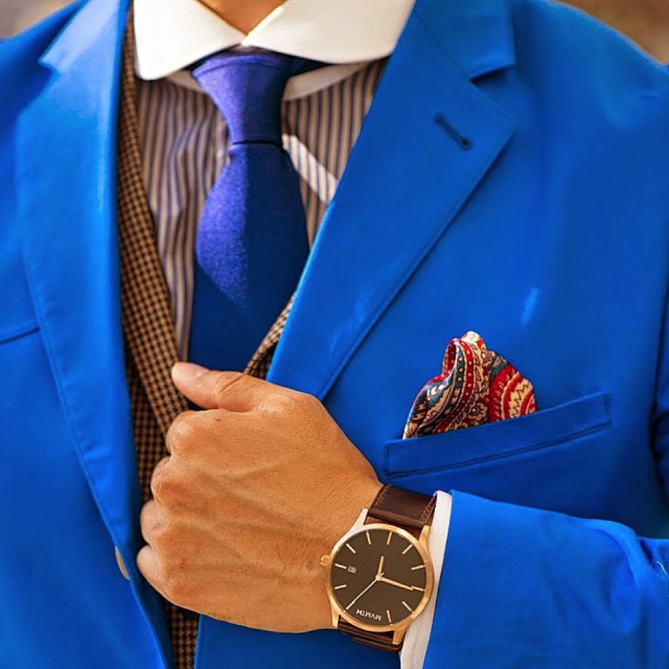 The Dark Knot's Waterbury Blue Solid Silk Tie over a striped shirt.