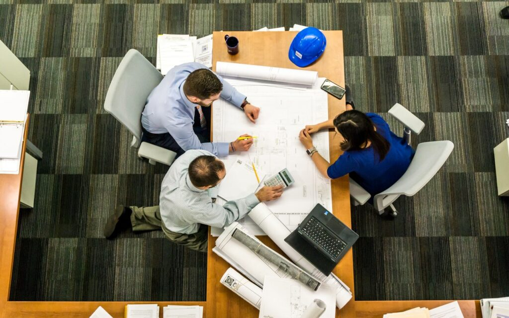 three people overhead shot at a desk looking at blueprints
