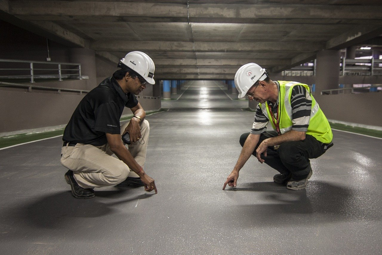 two men in construction observing the ground