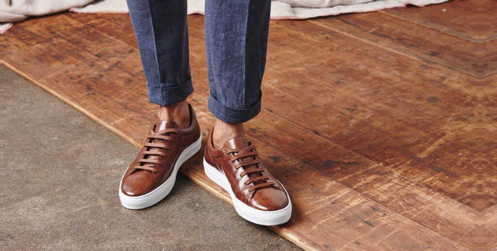 closeup of brown leather sneakers and blue pants