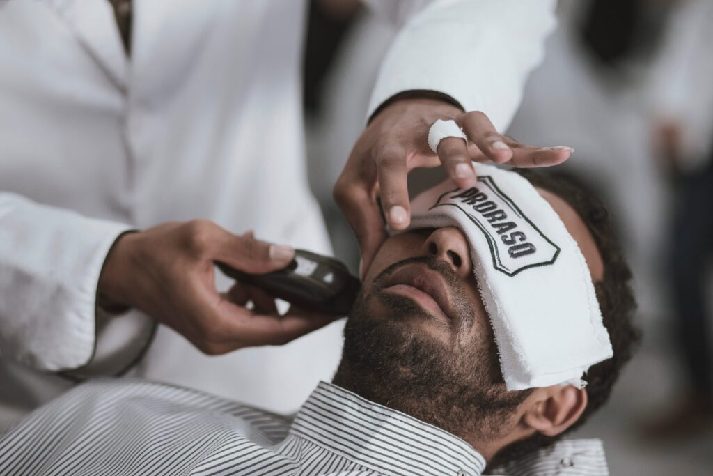 how to look younger - photo of man at barber getting shave