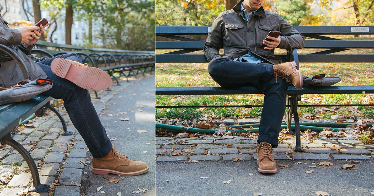 man on park bench wearing jeans and brown boots sitting with legs crossed