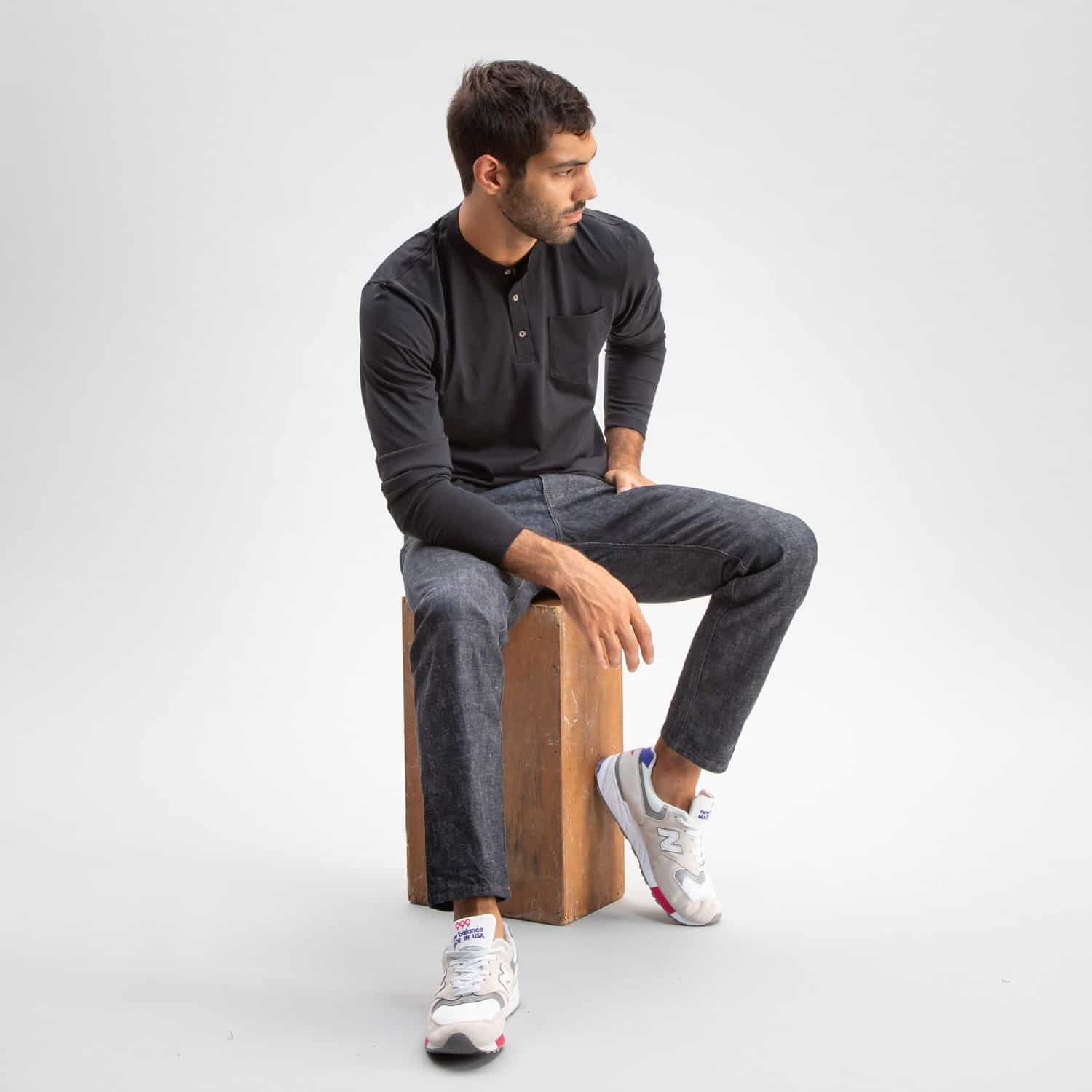 man sitting wearing charcoal pants and charcoal henley from todd shelton