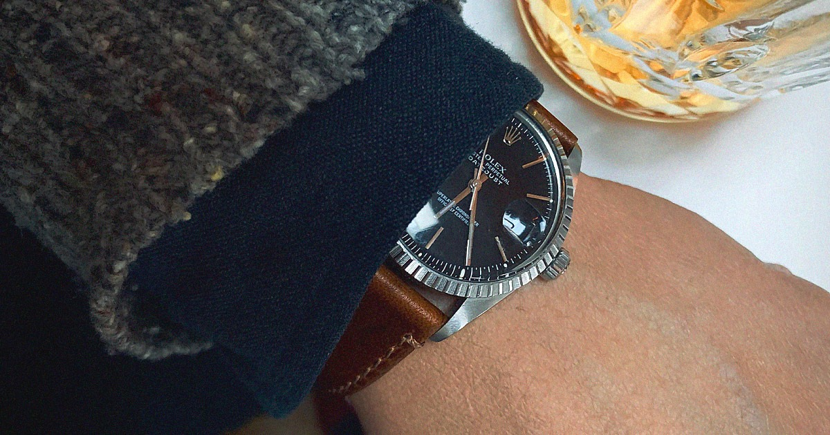 rolex watch with brown strap peeking out from under grey shirt cuff