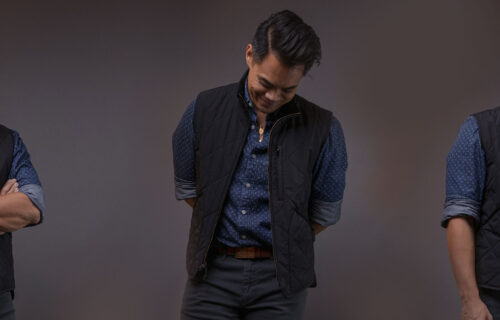 man wearing navy quilted vest with blue shirt