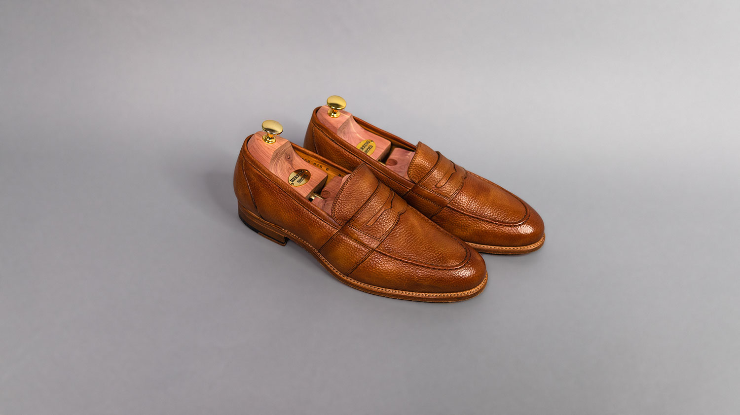 tan leather loafers from Herring on gray background