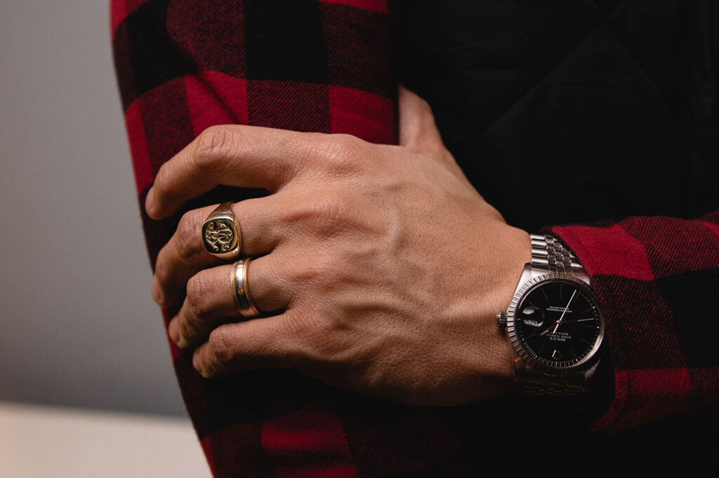 rebus signet ring with wedding ring and black dial rolex watch on left hand