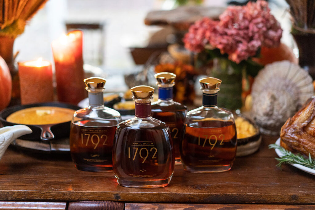 four bottles of bourbon on a Thanksgiving table setting - credit 1792 style