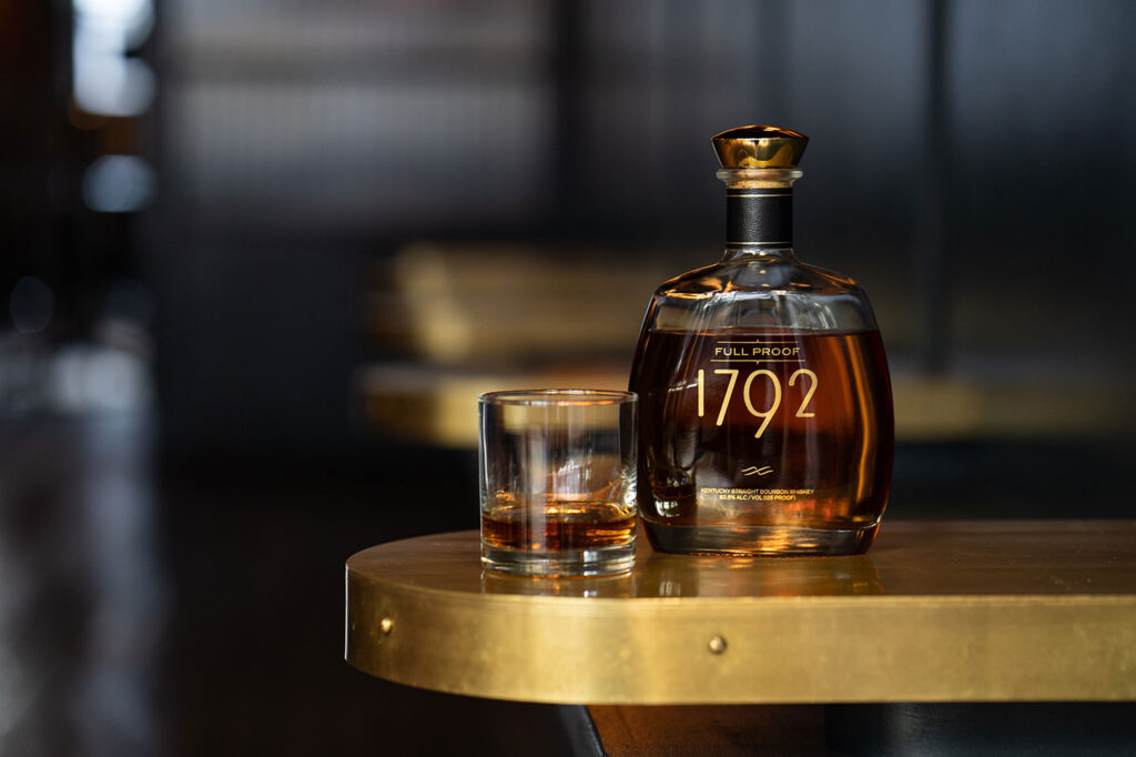 how to do a bourbon tasting - bourbon bottle and glass on brass bar top, credit 1792 style