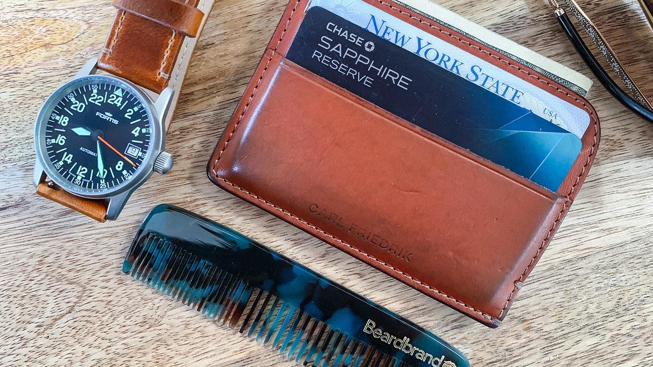 overhead shot of men's accessories, cardholder wallet, wristwatch, and pocket comb