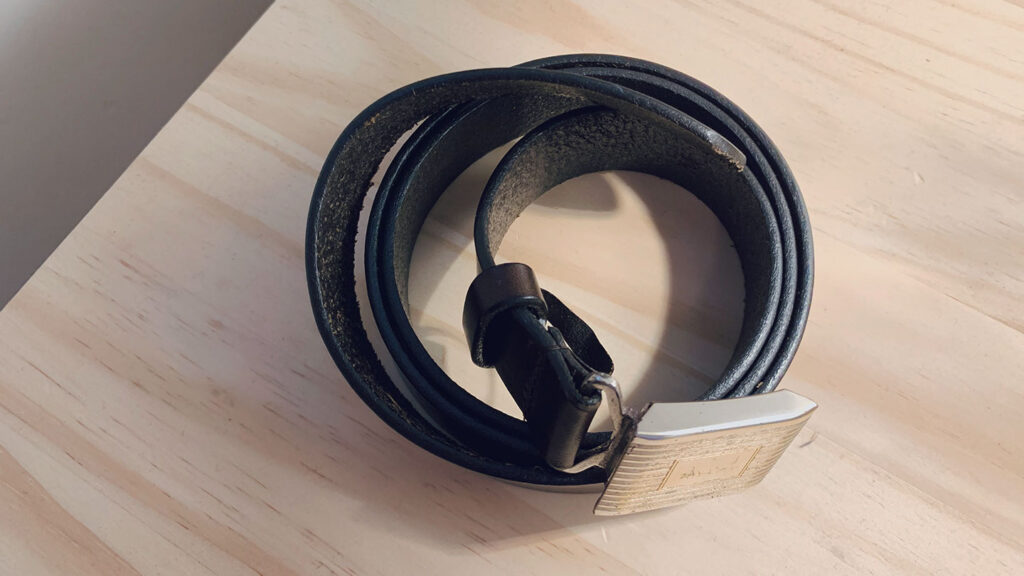 how to store belts - image of rolled up dark brown leather belt on wooden table