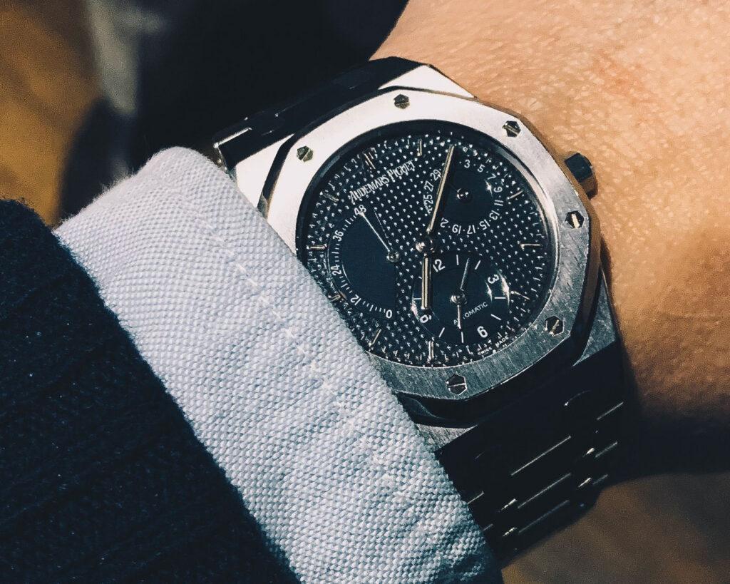 closeup of steel audemars piguet watch on wrist under shirt cuff