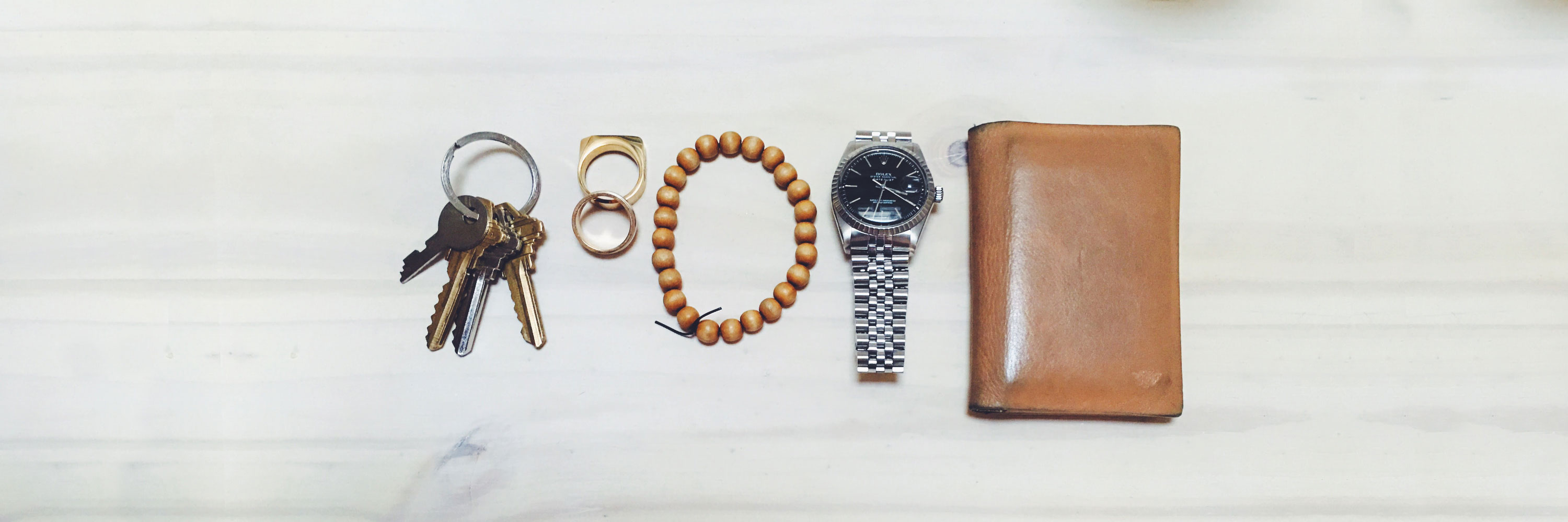 flatlay image of keys, rings, bracelet, watch, and wallet - the typical urban edc kit