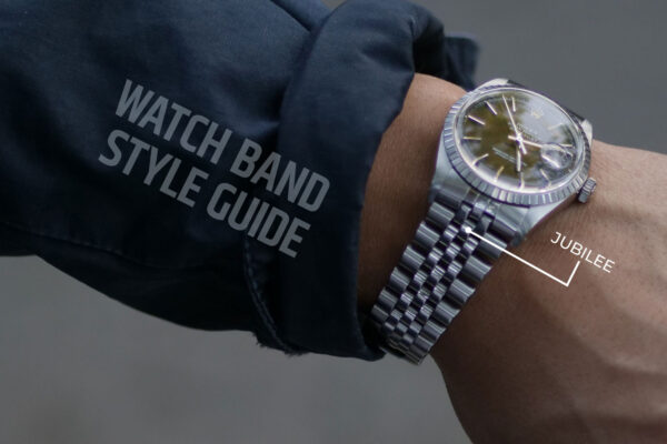 arm with navy jacket sleeve and steel rolex wristwatch