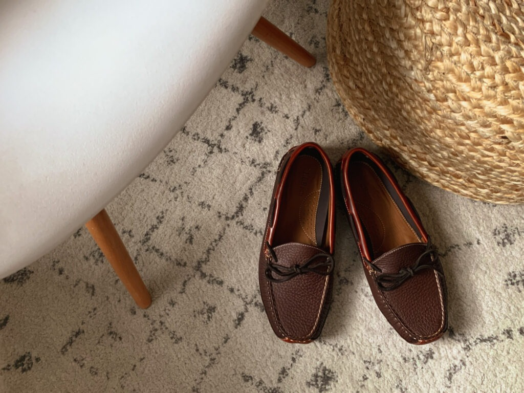 close up of llbean bison leather slippers on a light rug next to an ottoman and chair