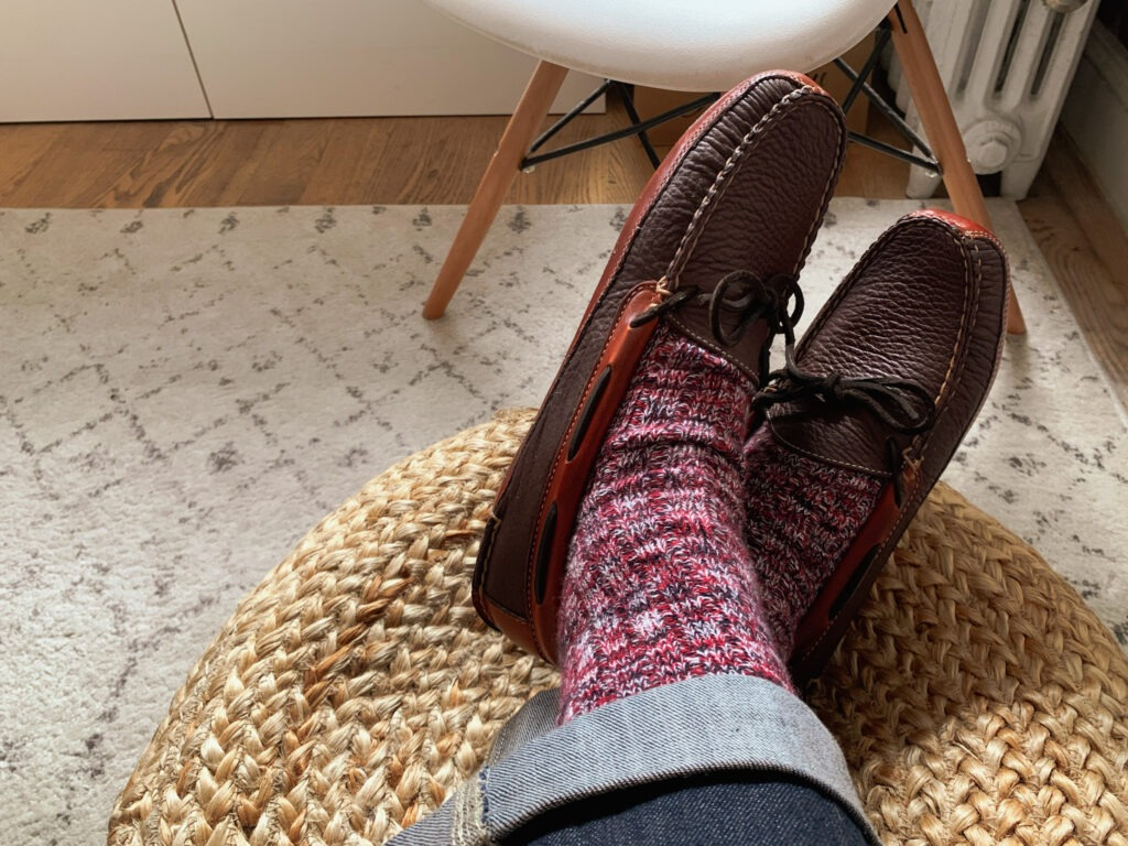 close up of man feet wearing burgundy wool socks with brown leather slippers in living room