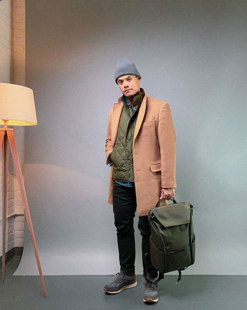man in tan overcoat green quilted vest and grey beanie