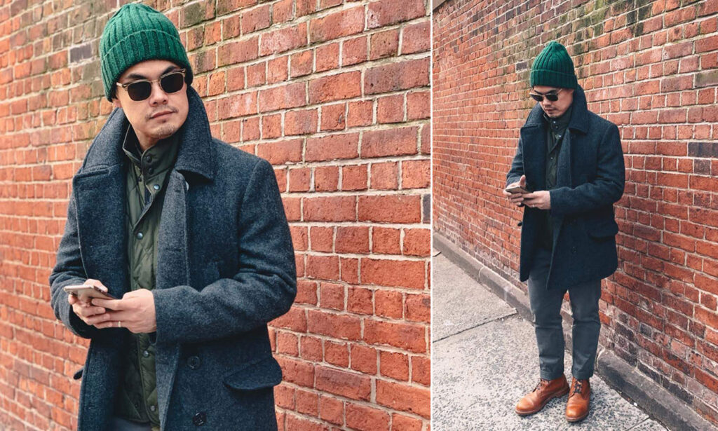 man wearing grey peacoat and green beanie and tan boots