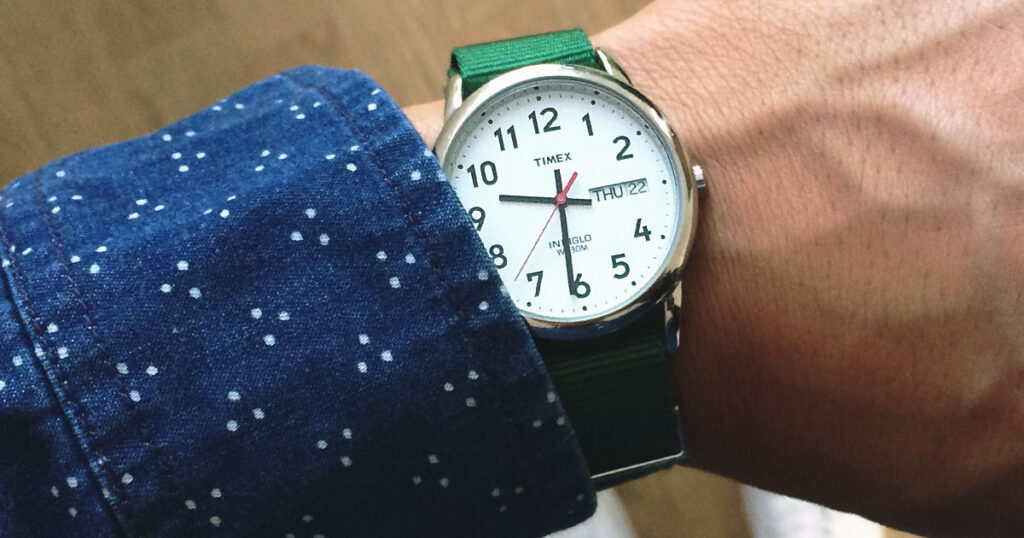 closeup of Timex watch on wrist with green strap and blue long sleeve shirt