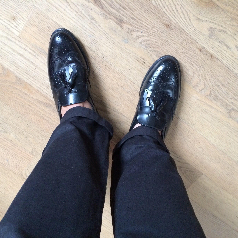 black leather wingtip kiltie tassel loafers.