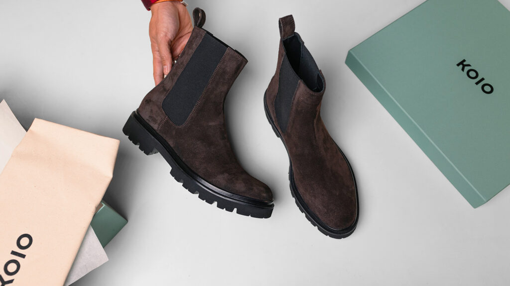 brown koio chelsea boots with box on table