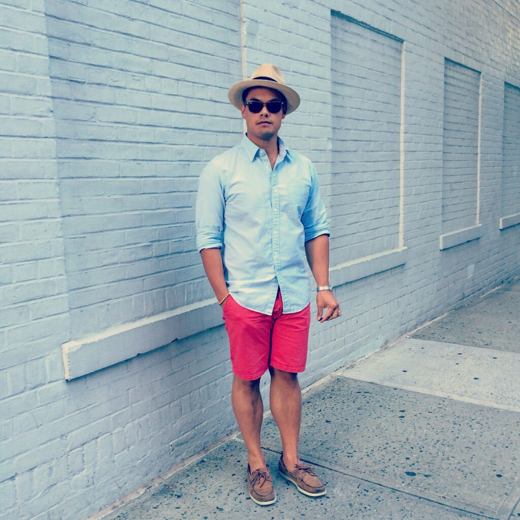 man wearing blue oxford shirt with red shorts and panama hat