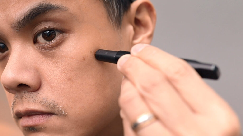 man applying concealer with stryx concealer tool