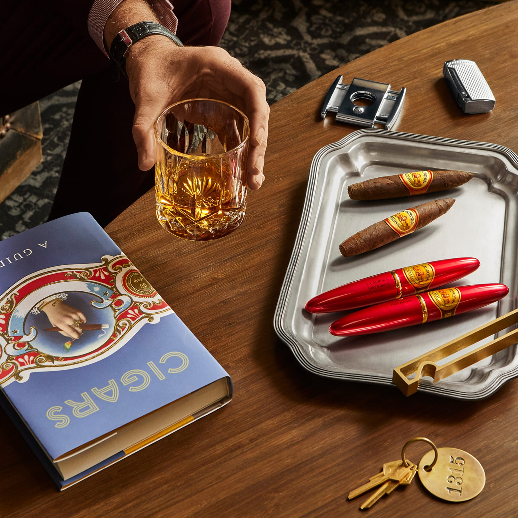 close up of tray with red cigar tubes and man's hand holding bourbon glass next to cigar book