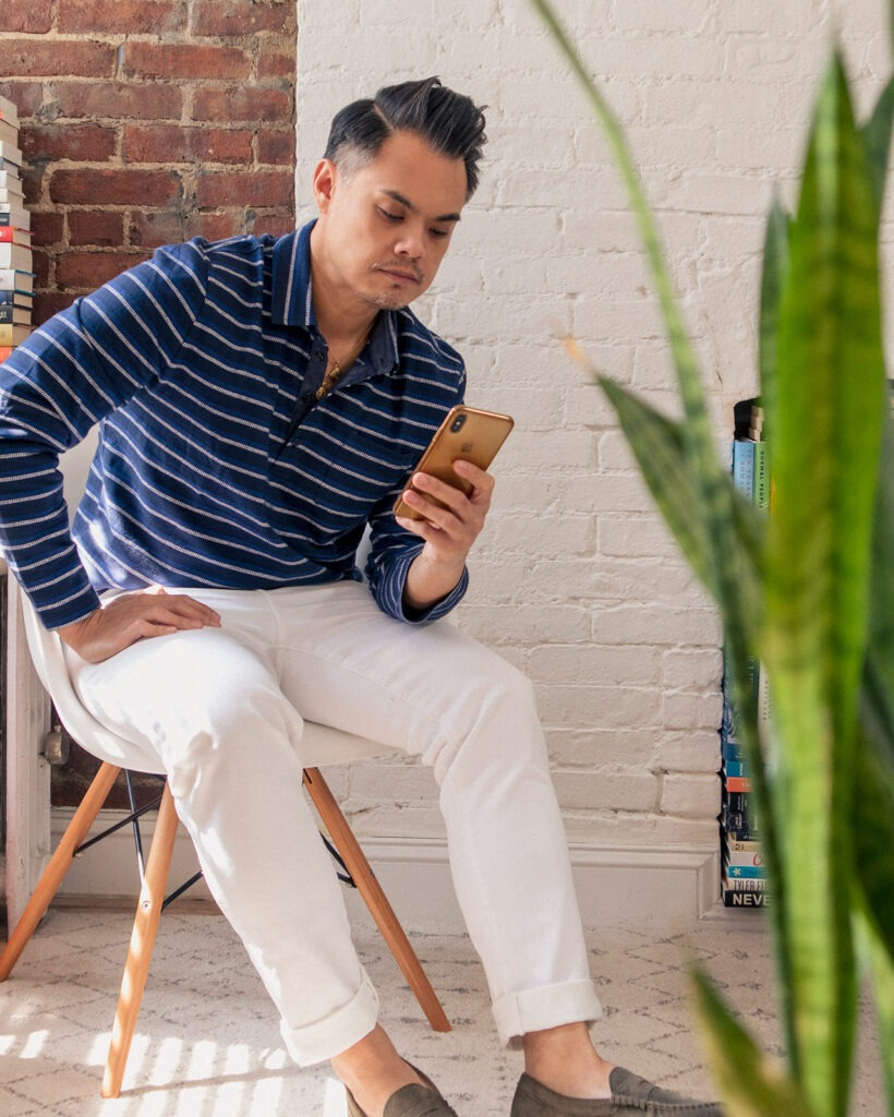 asian man in dark blue polo and white jeans on phone