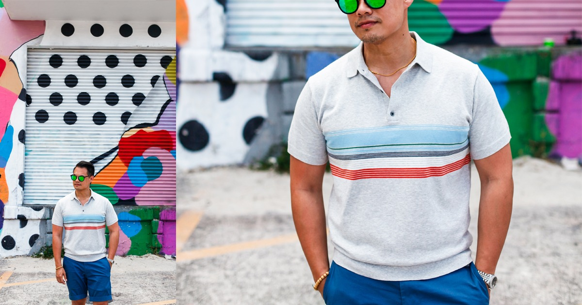 asian man wearing grey polo with multi colored stripes