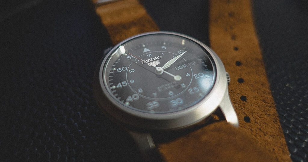 closeup of seiko 5 watch black dial with brown leather strap