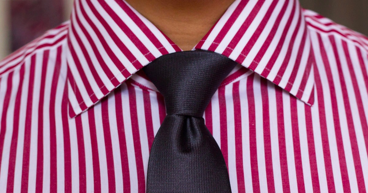 closeup of man wearing red stripe shirt and dark tie knot